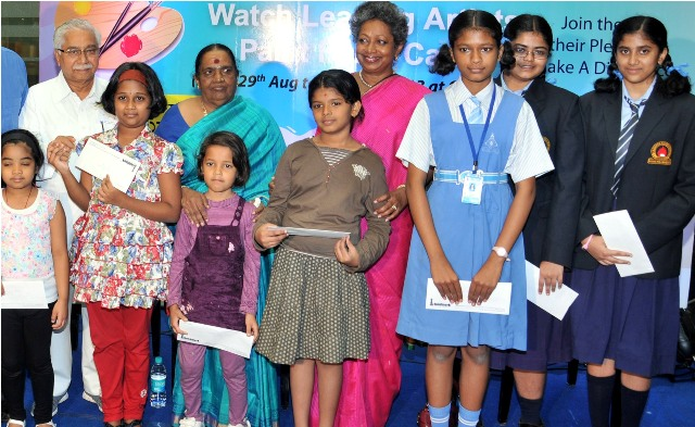 Children who won the painting competition pose with guests