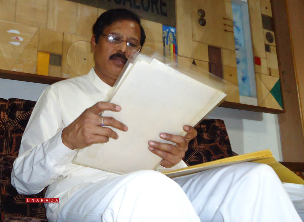 V.R.Sudarshan trying to justify his innocence by displaying relevant documents, in the press meet in Bengaluru, today. Photo: WWW.ENARADA.COM