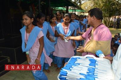 KISS founder Dr Achyuta Samanta gifting pens to tribal students writing Odisha board's tenth standard exams.